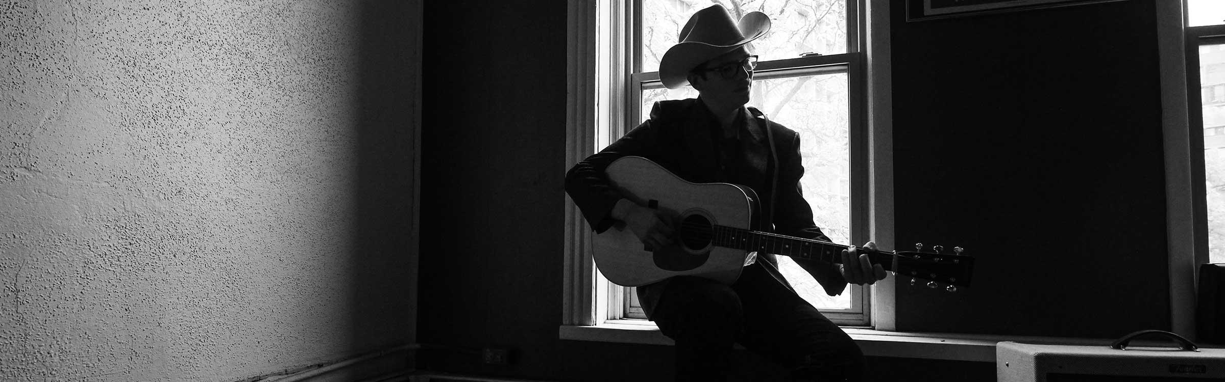 David Robinson sitting playing guitar